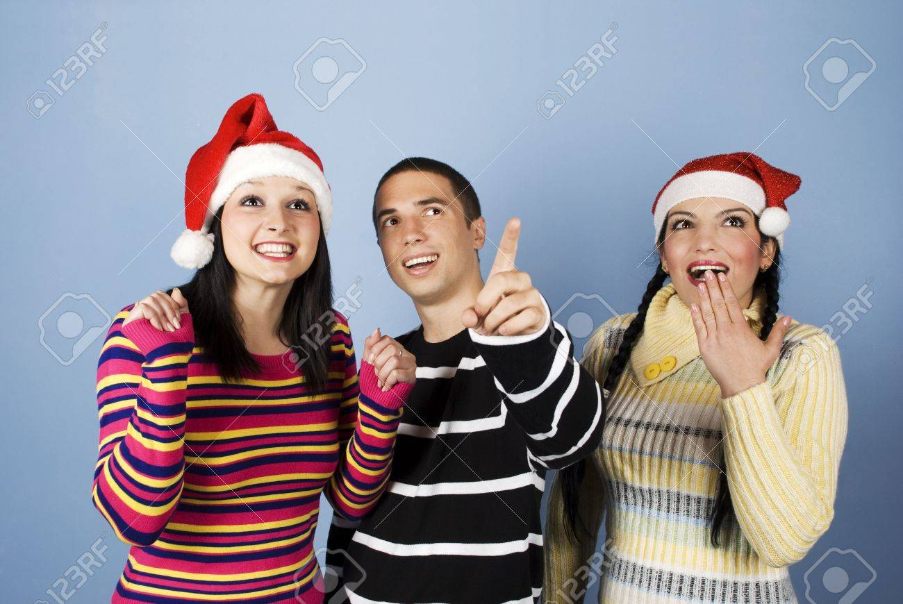 Christmas surprise with three friends,the man showing something and they all are surprised,happy and laughing together.(You can add in photo gifts,presents,promotions or snowflakes) Stock Photo - 5858734