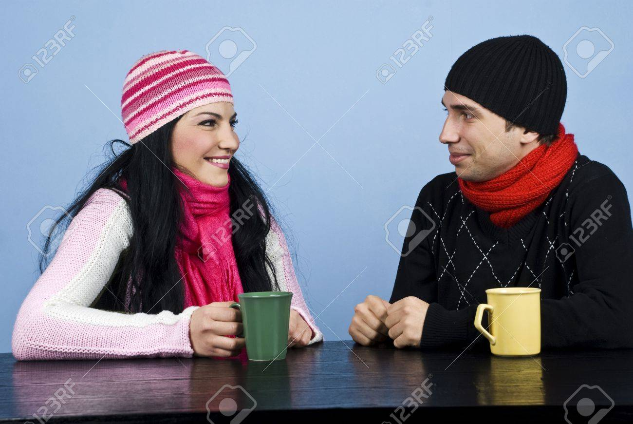 Young couple having a funny conversation and standing  face to face at table enjoying a cup of tea together Stock Photo - 6013980