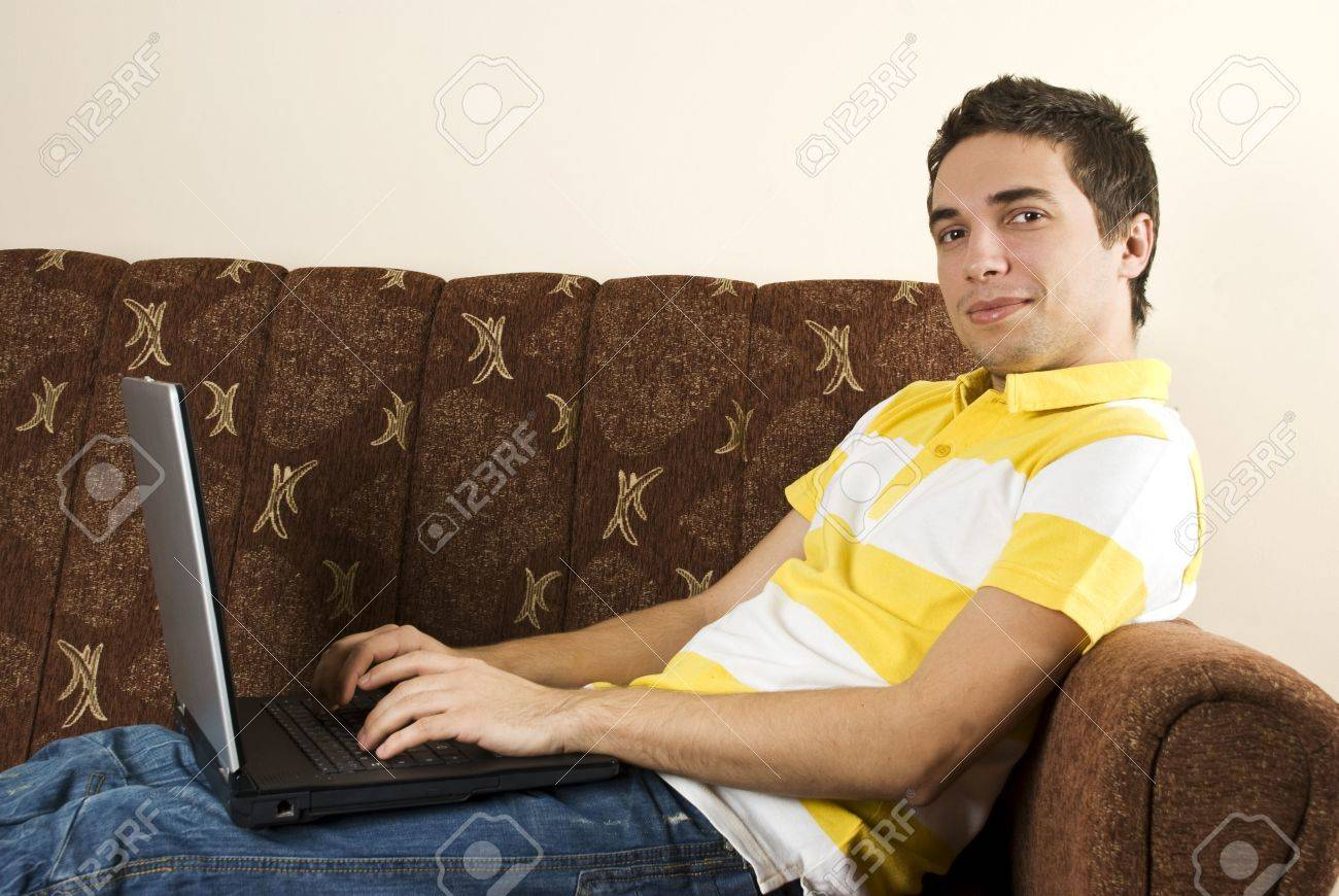 Relaxed Guy Sitting In Sofa And Using Laptop,he Looking At You ...