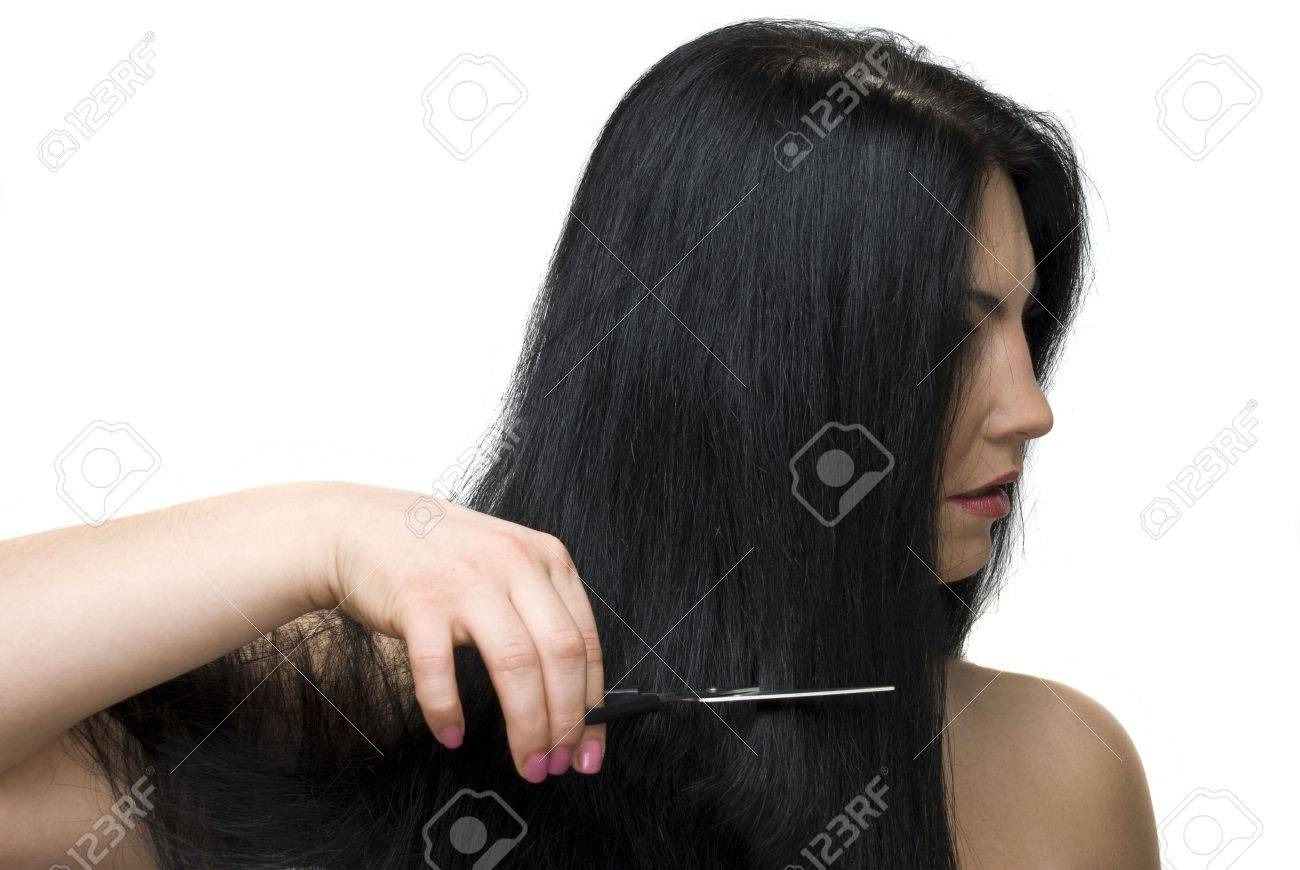 Beautiful brunette woman standing in profile and cutting her long hair with a scissors Stock Photo - 6353005