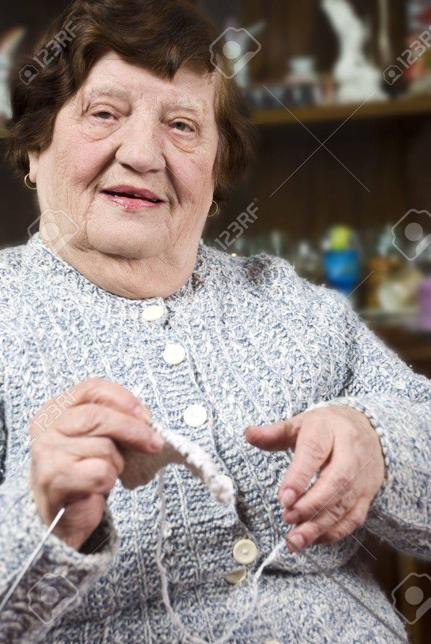 Cheerful grandma holding knit with needles and wool ball preparing for knitting in her living room Stock Photo - 6385074