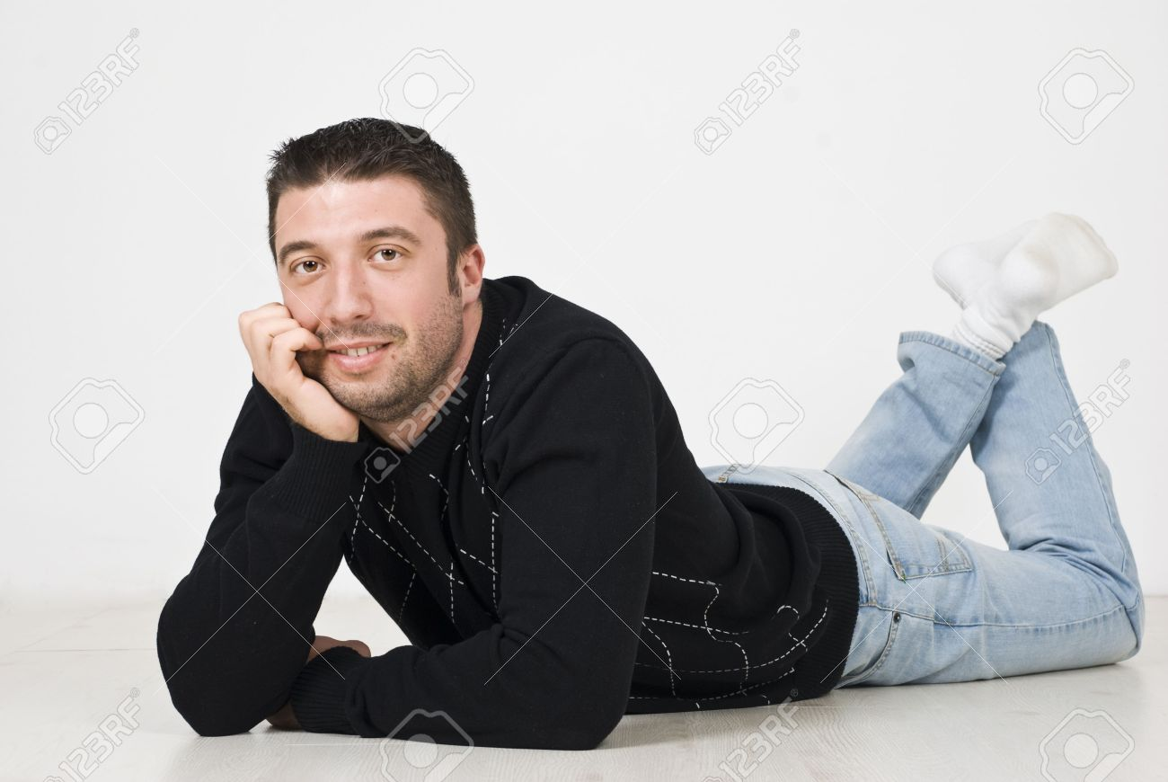 Happy Young Man Lying Down On Wooden Floor With Hand On Chin Stock