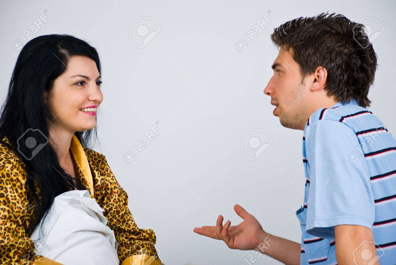 Close up of young couple on bed having an conversation and the man explaining something to his wife Stock Photo - 6960511