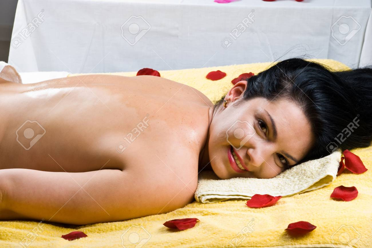 Happy smiling woman lying on massage table and having her back with oil Stock Photo - 7040690