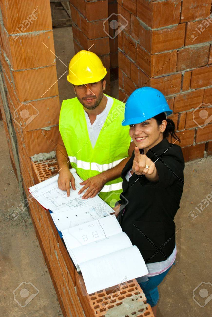 Two architects in a house under construction having a discussion and the woman pointing up to you Stock Photo - 7310539