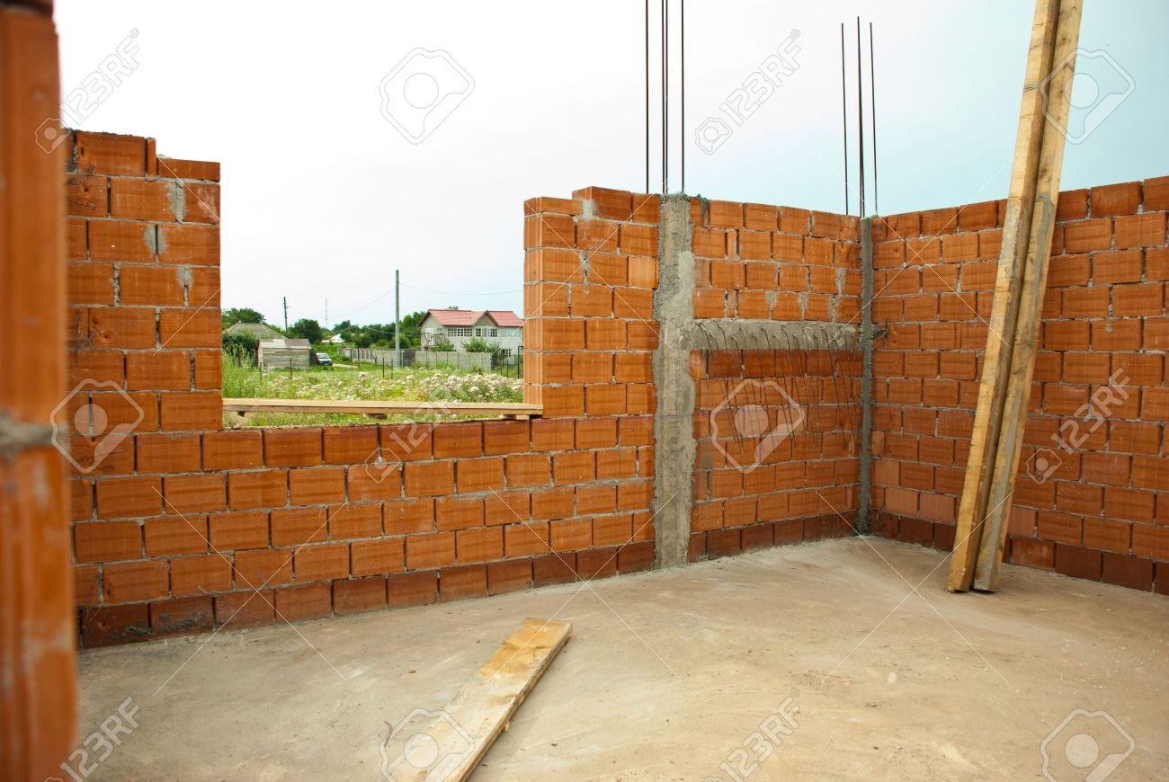 interior of a house under construction with red brick walls stock
