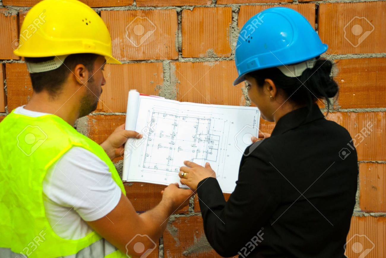 Back of two architects with helmet working in a house under construction and holding blueprints,selective focus on plan Stock Photo - 7334482