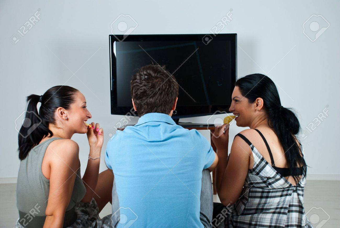 Three friends having a funny conversation while watching soccer game at tv and eating chips - 7334493