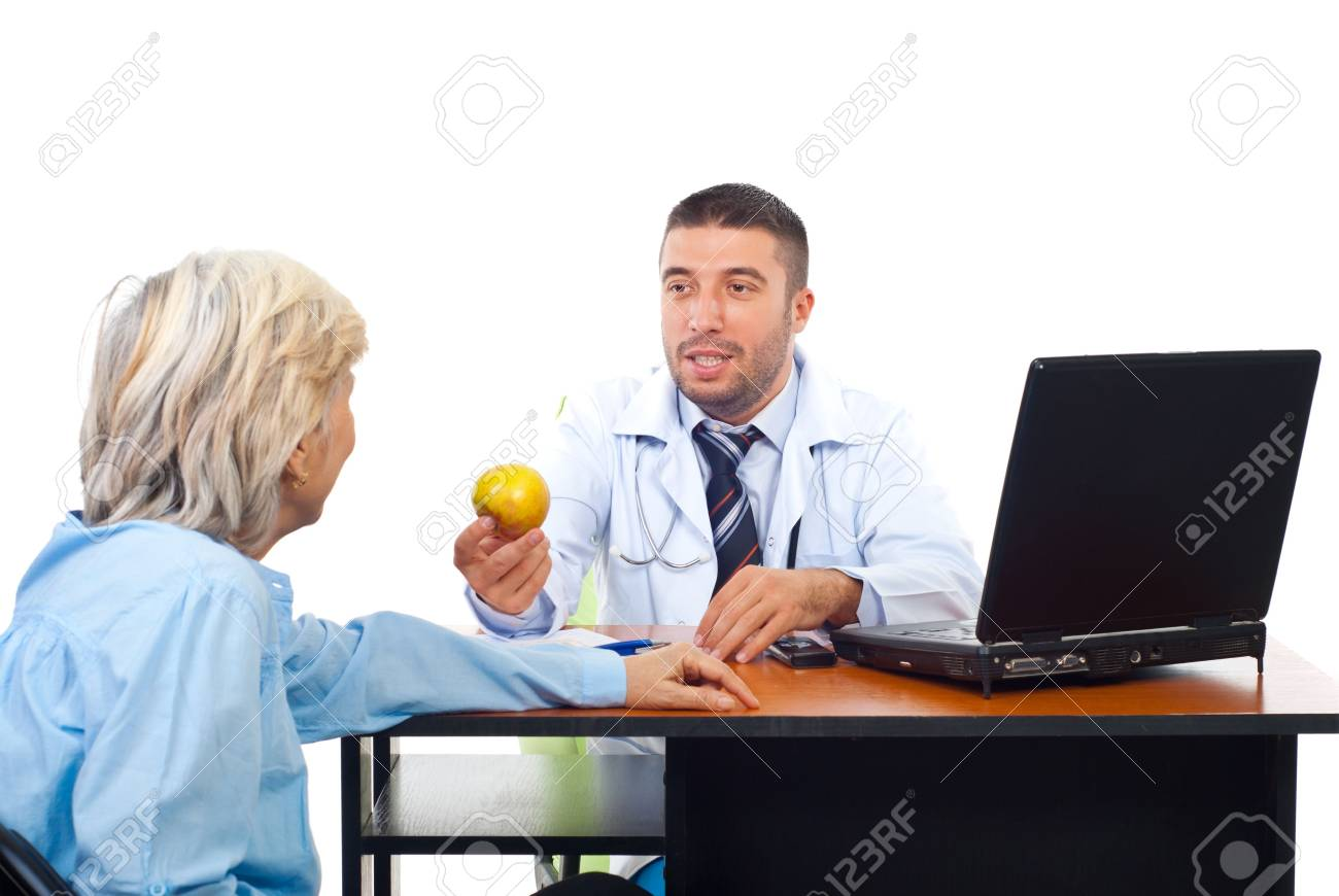 Doctor male offering an apple to a senior woman patient in his office Stock Photo - 8042058