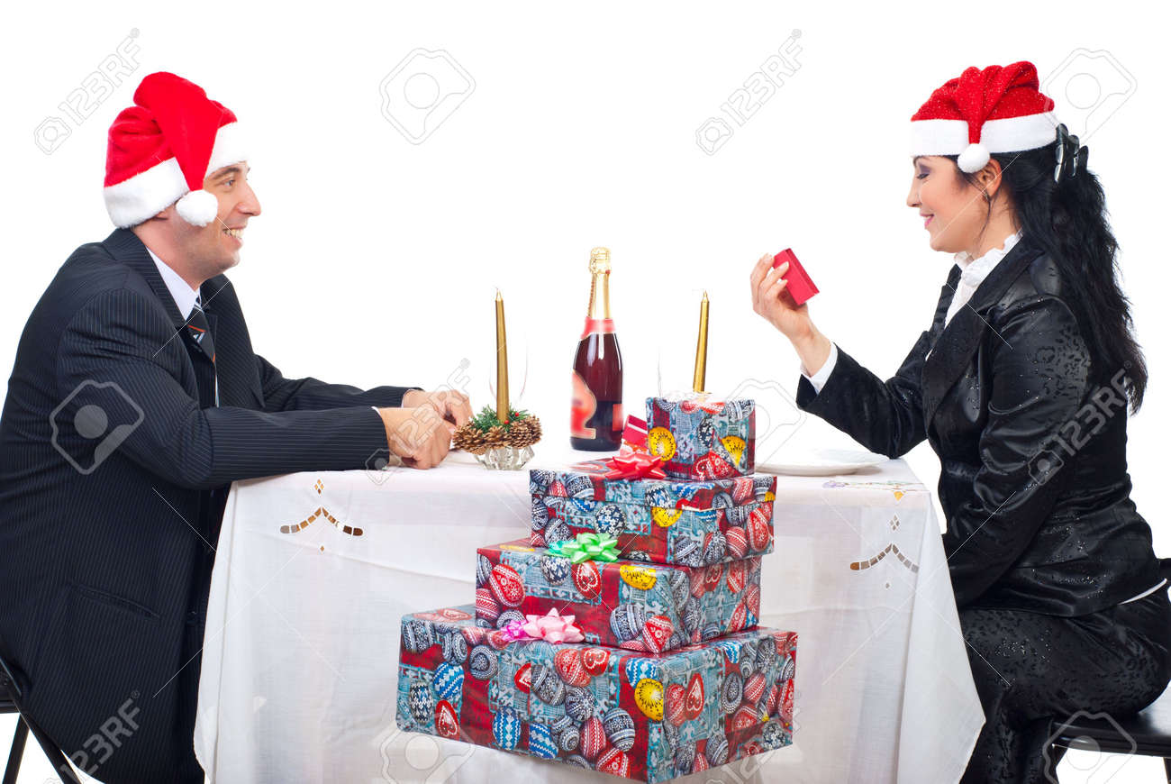 Happy couple enjoy Christmas night  sitting at table with presents  , woman received a gift and looking to box Stock Photo - 8042196