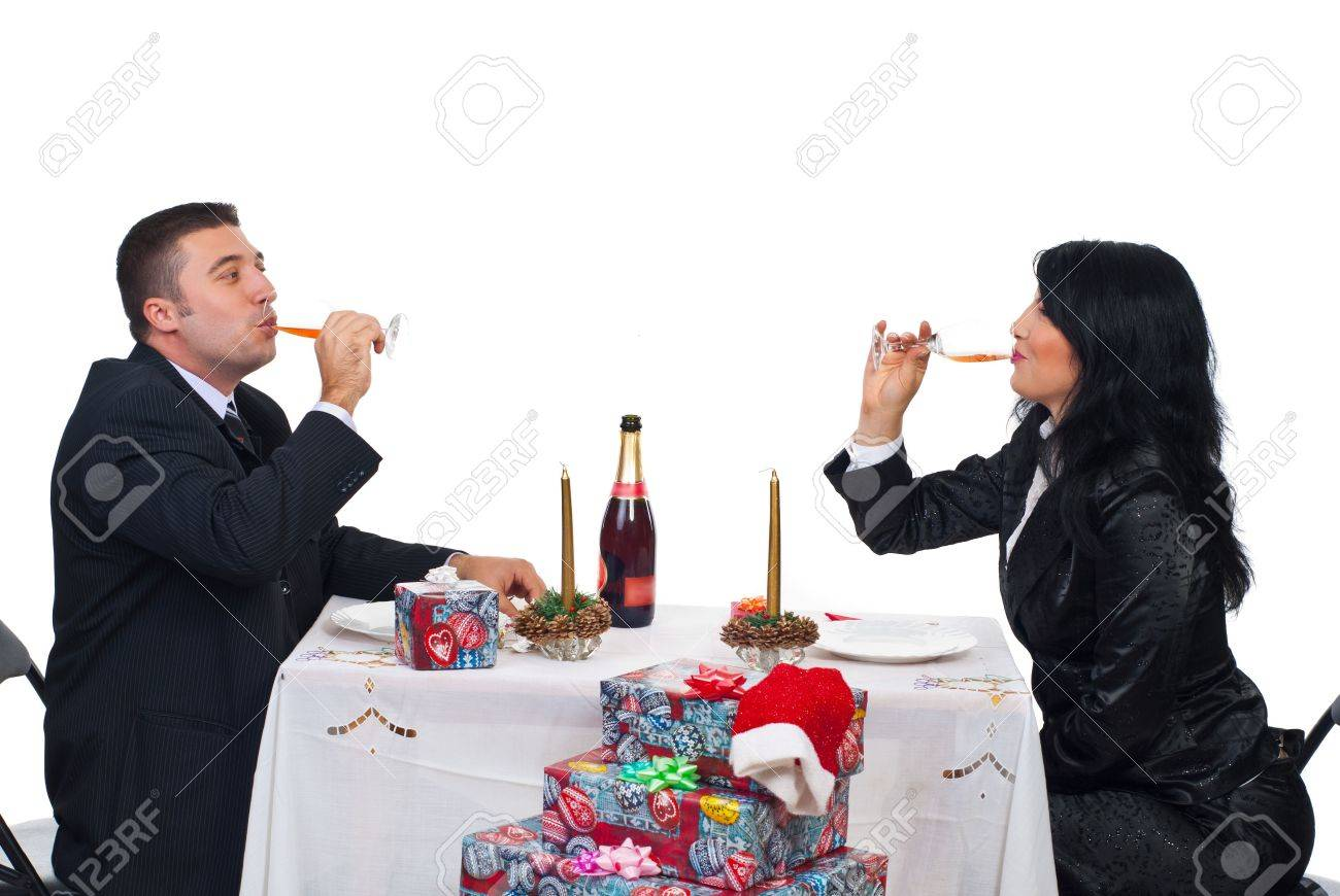 Elegant couple in festive clothes driking champagne and sitting together at Christmas table Stock Photo - 8042188