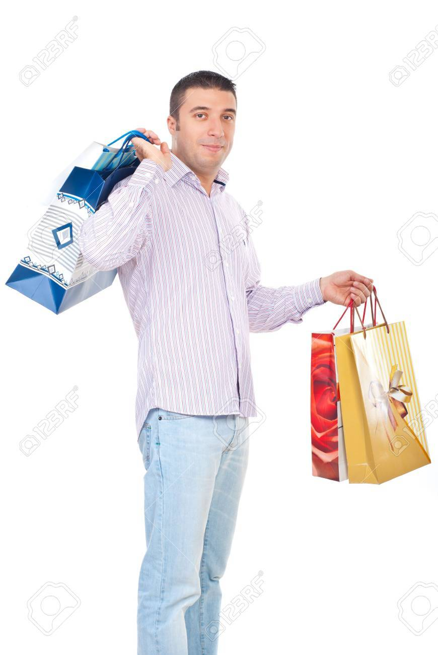 Shopper man carrying shopping bags and smiling isolated on white background Stock Photo - 8103082