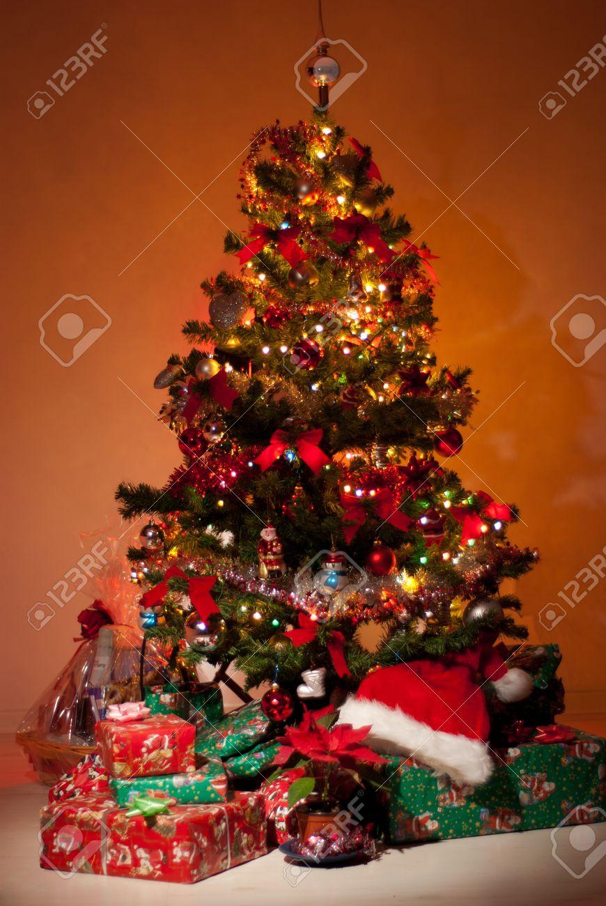 Schöne Weihnachtsbaum Mit Geschenke, Blumen Und Lichter Glühend In ...
