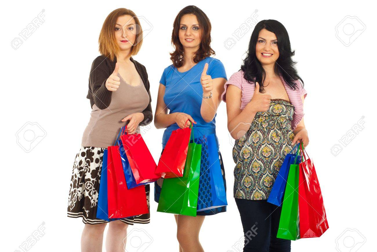 Three women standing in a row giving thumbs up and holiding colorful shopping bags isolated on white background Stock Photo - 9617546