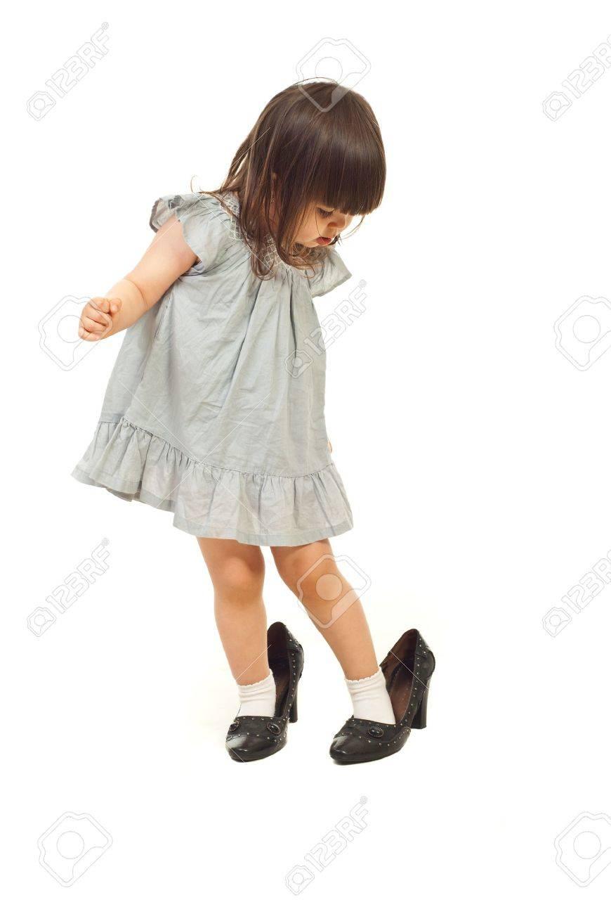 041a37eda0 Foto de archivo - Niña niño zapatos grandes y mirando hacia abajo con cara  atento aislada sobre fondo blanco
