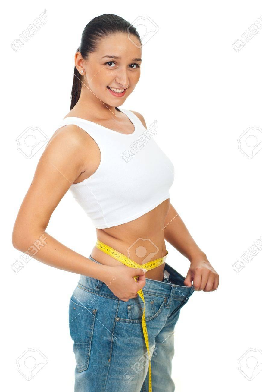 8d4962b873b Feliz mujer delgada en pantalones vaqueros grandes de medición de la  cintura con un centímetro aisladas