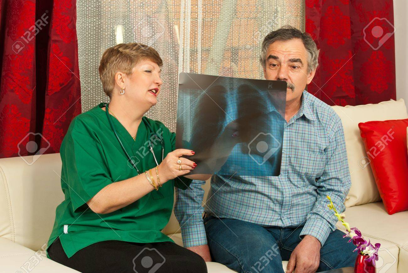 doctor woman showing x-ray to surprised mature patient male in