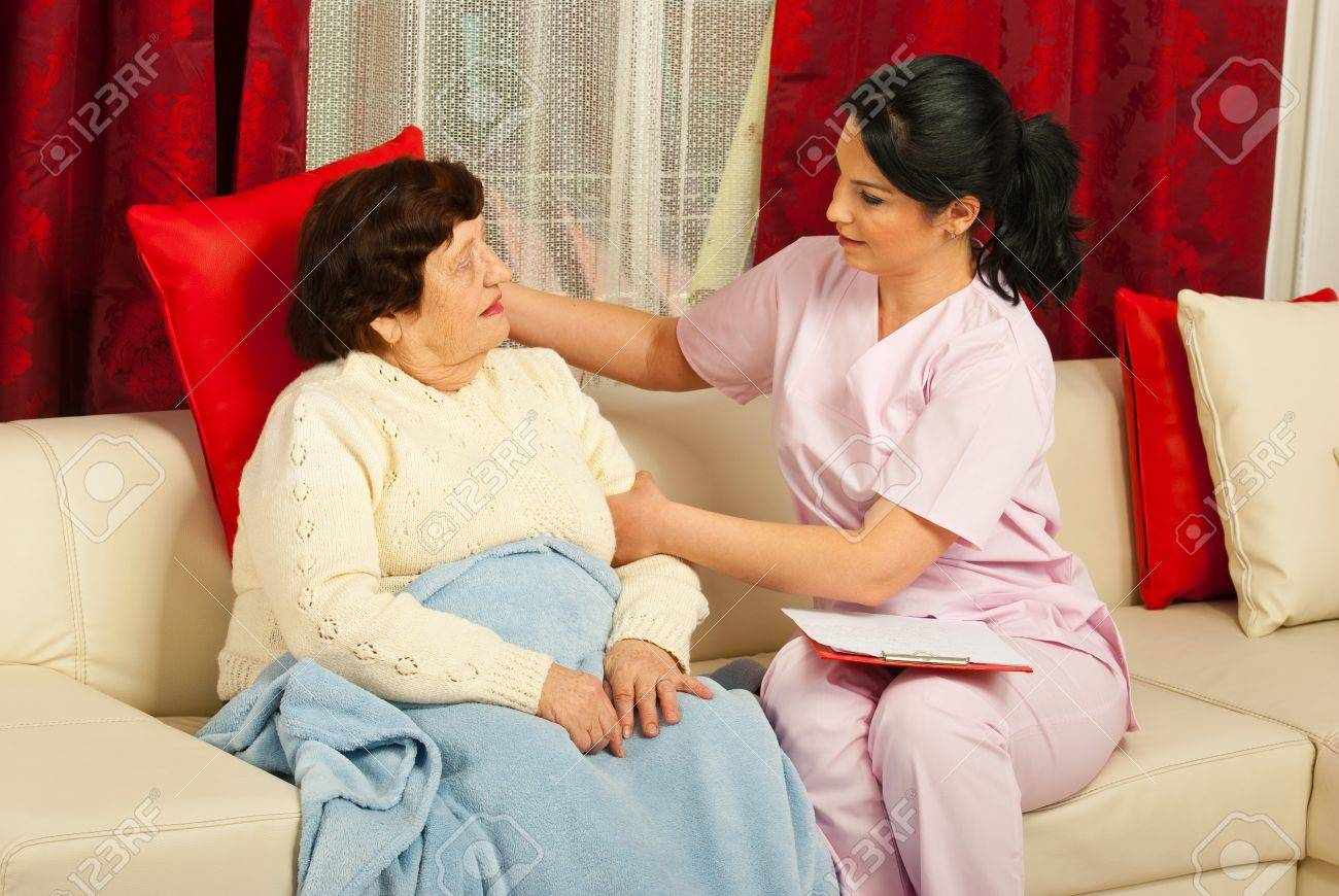Nurse caring a senior woman patient home and put a pillow to stay better on couch Stock Photo - 12922313