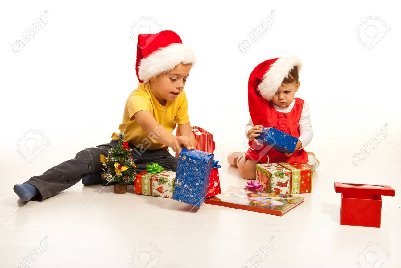 Two kids arrange  Christmas gifts and sitting together on floor Stock Photo - 16141877