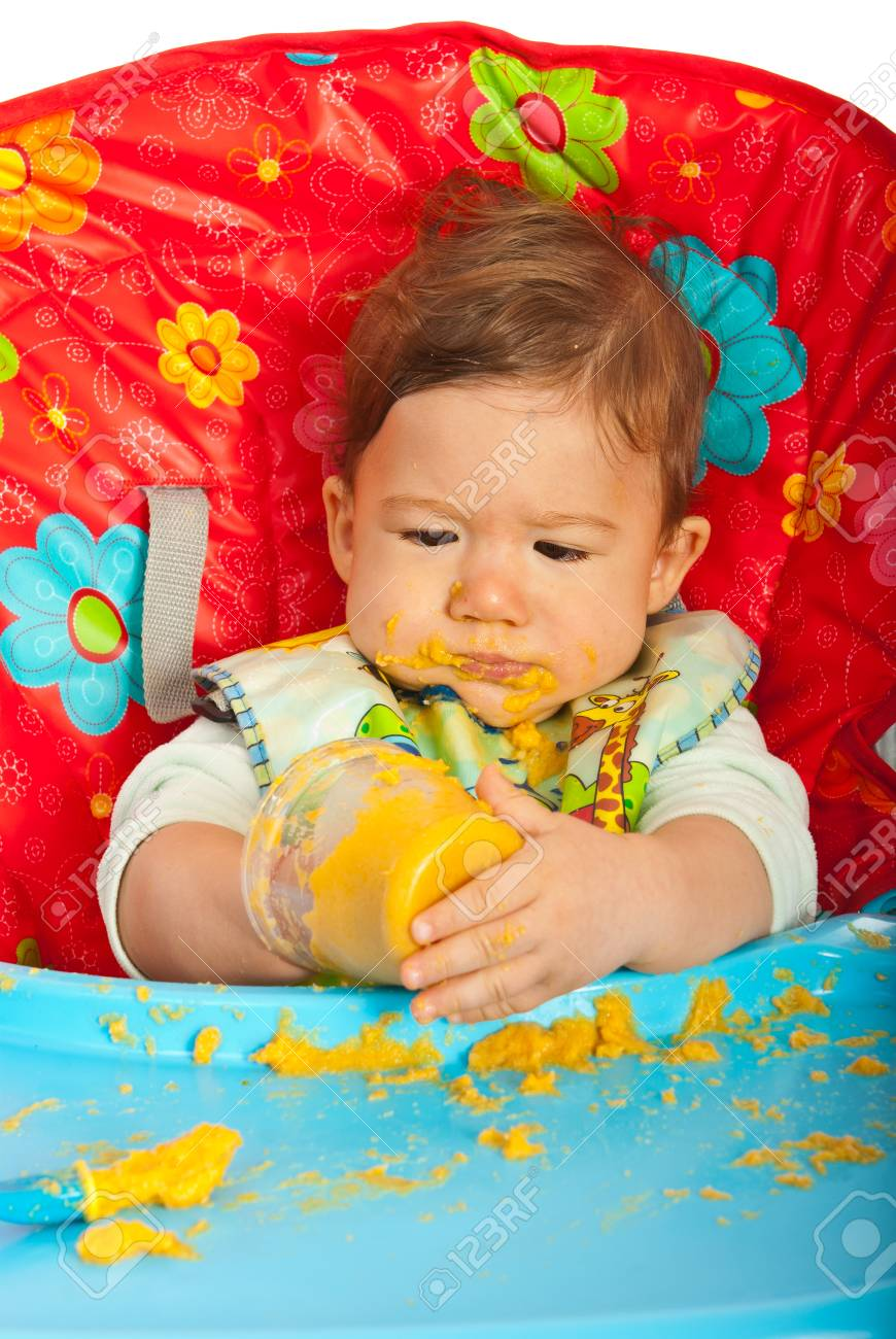 Messy baby boy eating puree by yourself and sitting in chair Stock Photo - 22788827