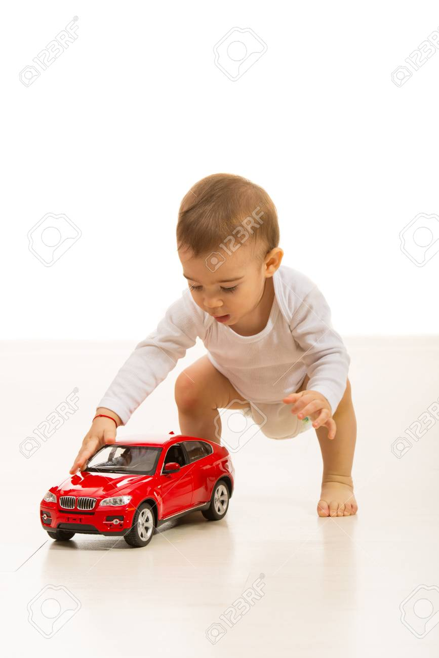 Baby Boy Playing With Car Toy Home And Standing On The Floor Stock
