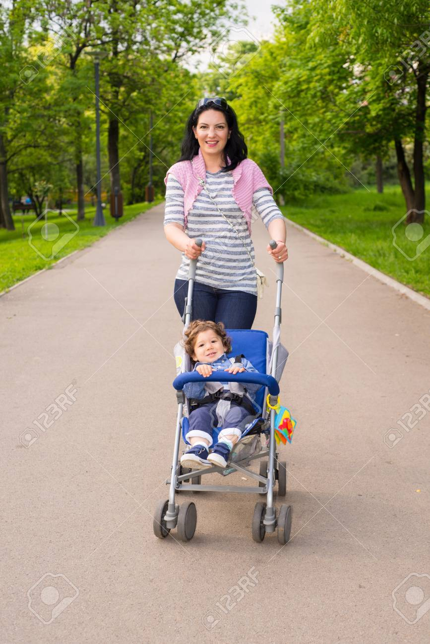 b831494d8e40 Happy Mom Pushing Pram With Toddler Boy In Park Stock Photo