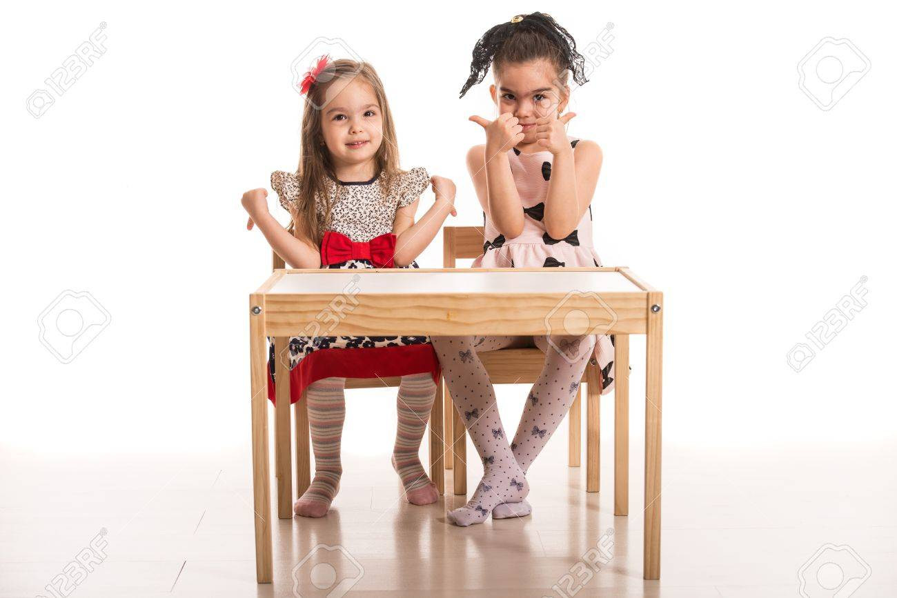 Two Girls Sitting On Chairs At Table And One Of Give Thumb Stock Photo Picture Royalty Free Image 39276618