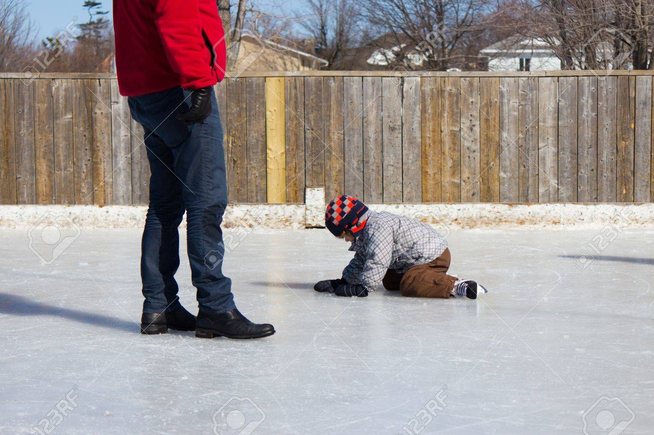 Father Teaching Son How To Ice Skate At An Outdoor Skating Rink In Winter  Stock Photo