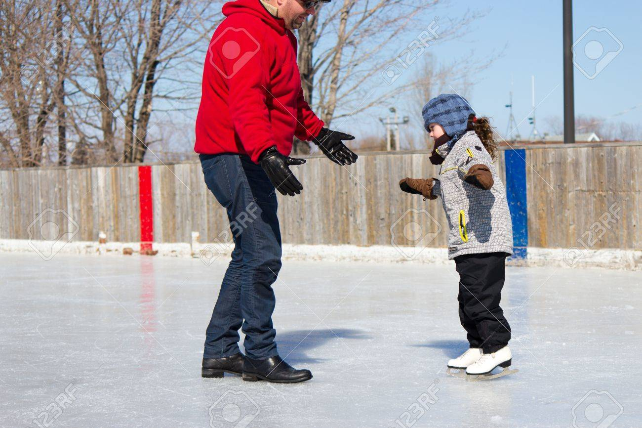 Father Teaching Daughter How To Ice Skate At An Outdoor Skating Rink In  Winter Stock Photo