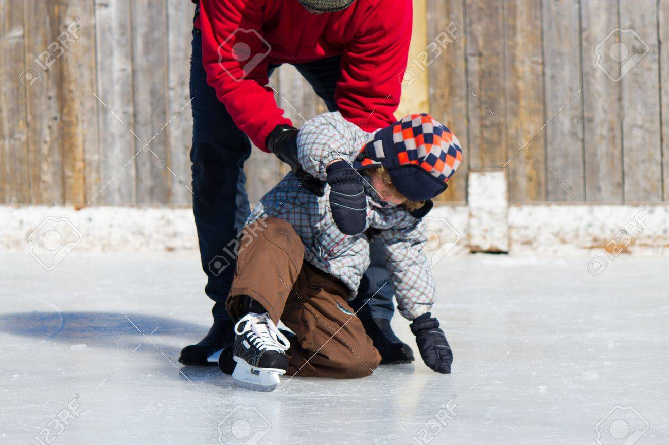 Father Teaching Son How To Ice Skate At An Outdoor Skating Rink In Winter  Stock