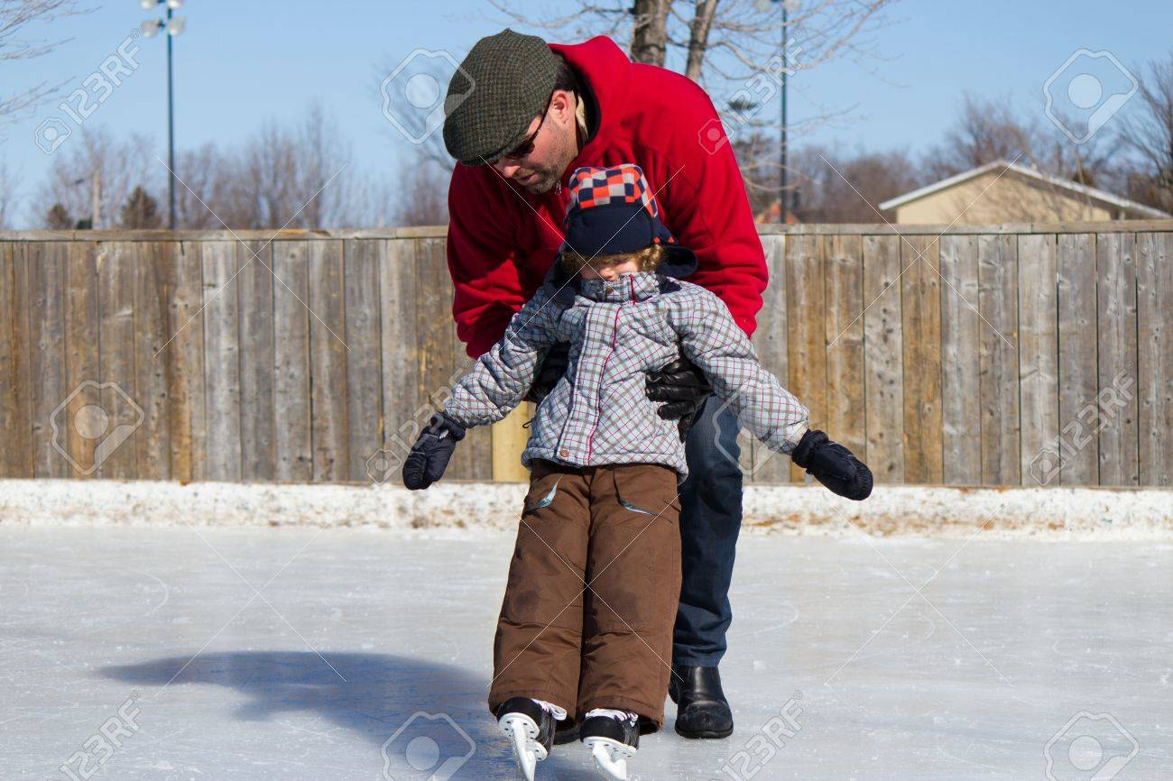 Father Teaching Son How To Ice Skate At An Outdoor Skating Rink In Winter  Stock Father