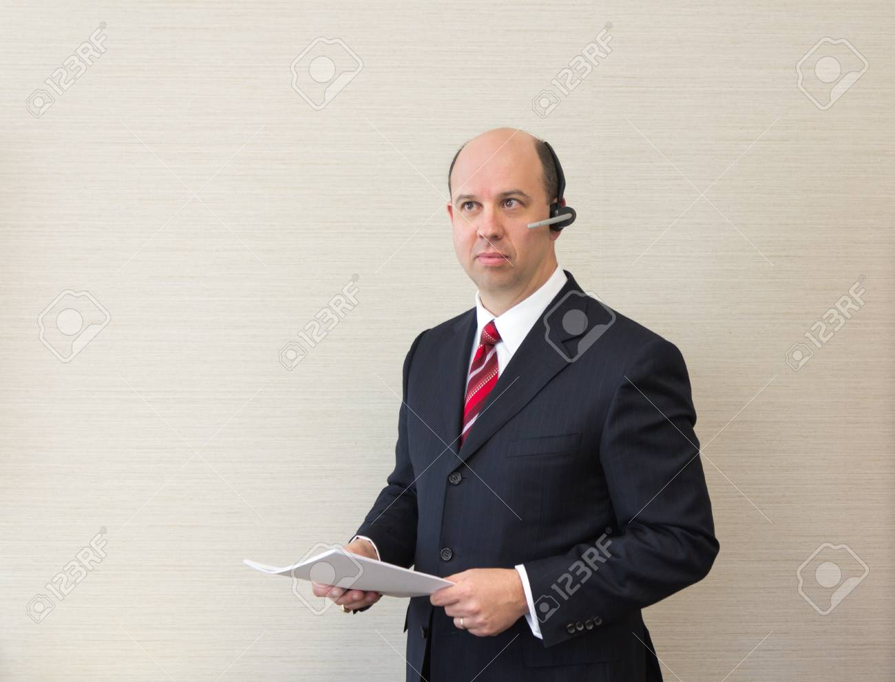Business man with a handsfree telephone headset holding a document. Stock Photo - 14124178