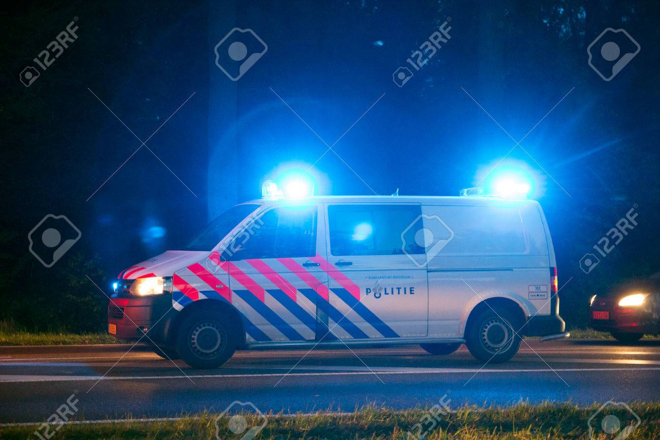 VARSSEVELD, NETHERLANDS - OCT 29, 2015: A Dutch police car with emergency lights holding traffic during a car accident. - 48184717