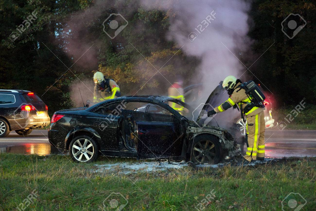Firefighters near a burned out car wreck - 48184724
