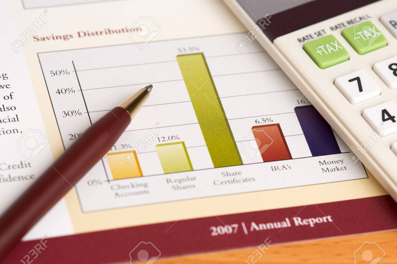 financial planning and review of year end reports pen and financial planning and review of year end reports pen and calculator on wood desktop