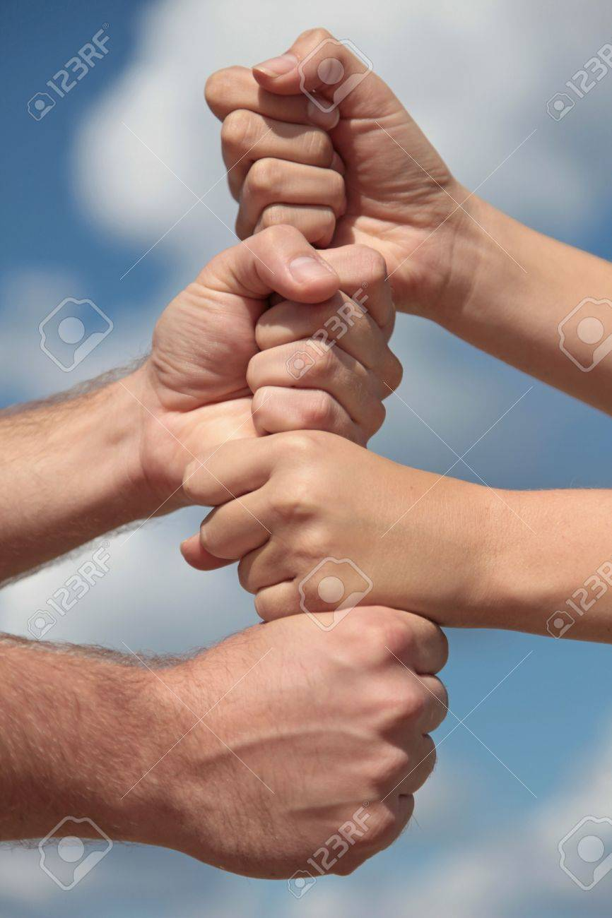 Some people putting her hands together in front of a bright blue sky. Stock Photo - 6293626