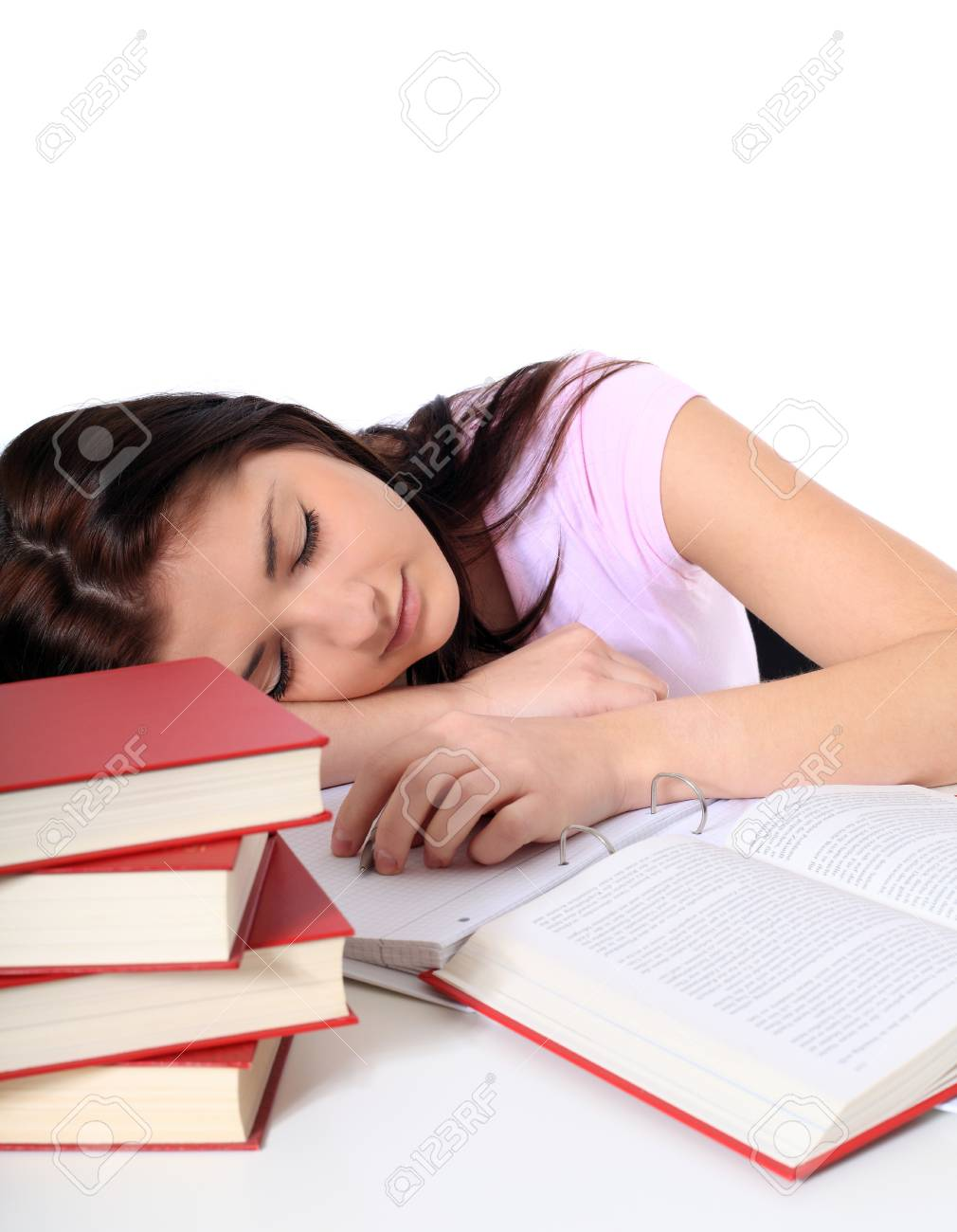 Attractive young woman is taking a nap on her study documents. All on white background. Stock Photo - 8504817
