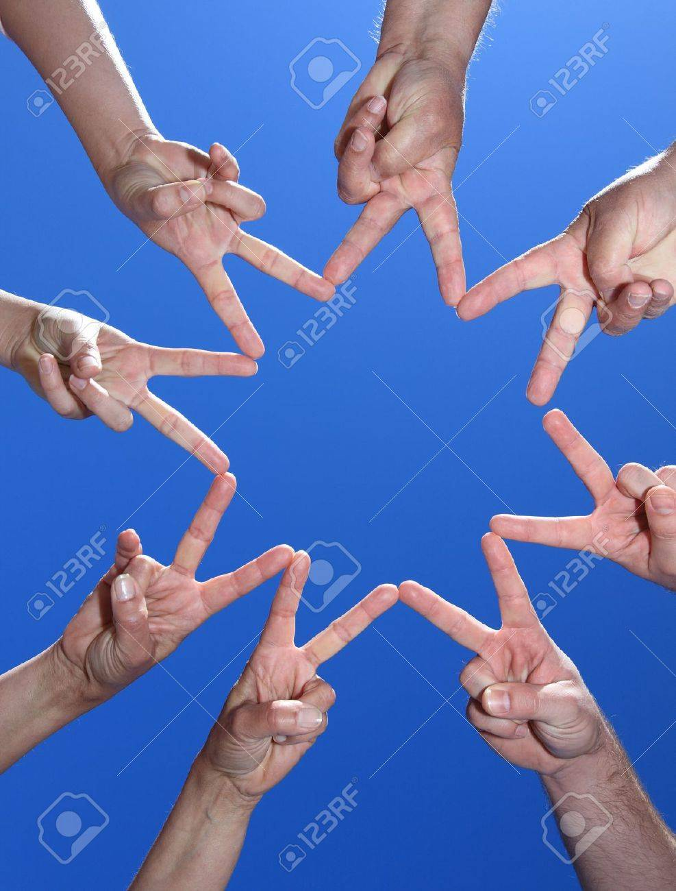 Various peoples hands in front of bright blue sky. Stock Photo - 9726341
