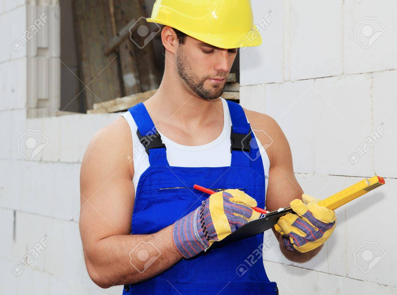Manual Worker On Construction Site Writing On Clipboard. Stock ...