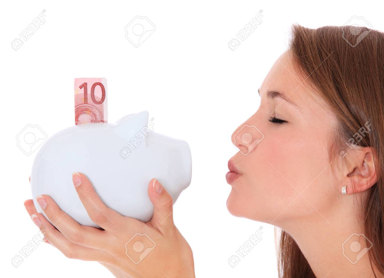 Attractive young woman kissing piggy bank. All on white background. Stock Photo - 10160168