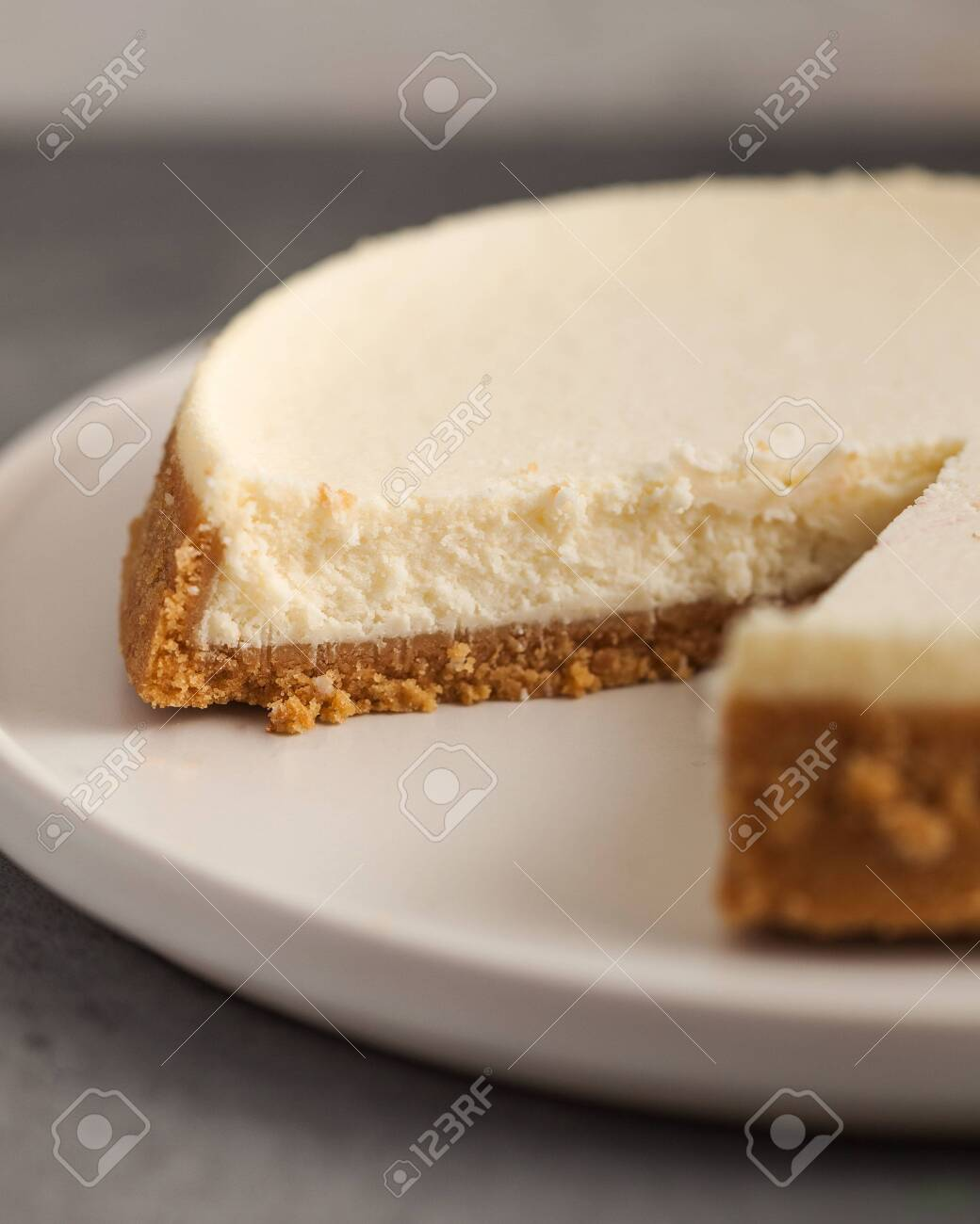 Cut cheesecake cake close-up on a white plate on a gray background. - 135717583