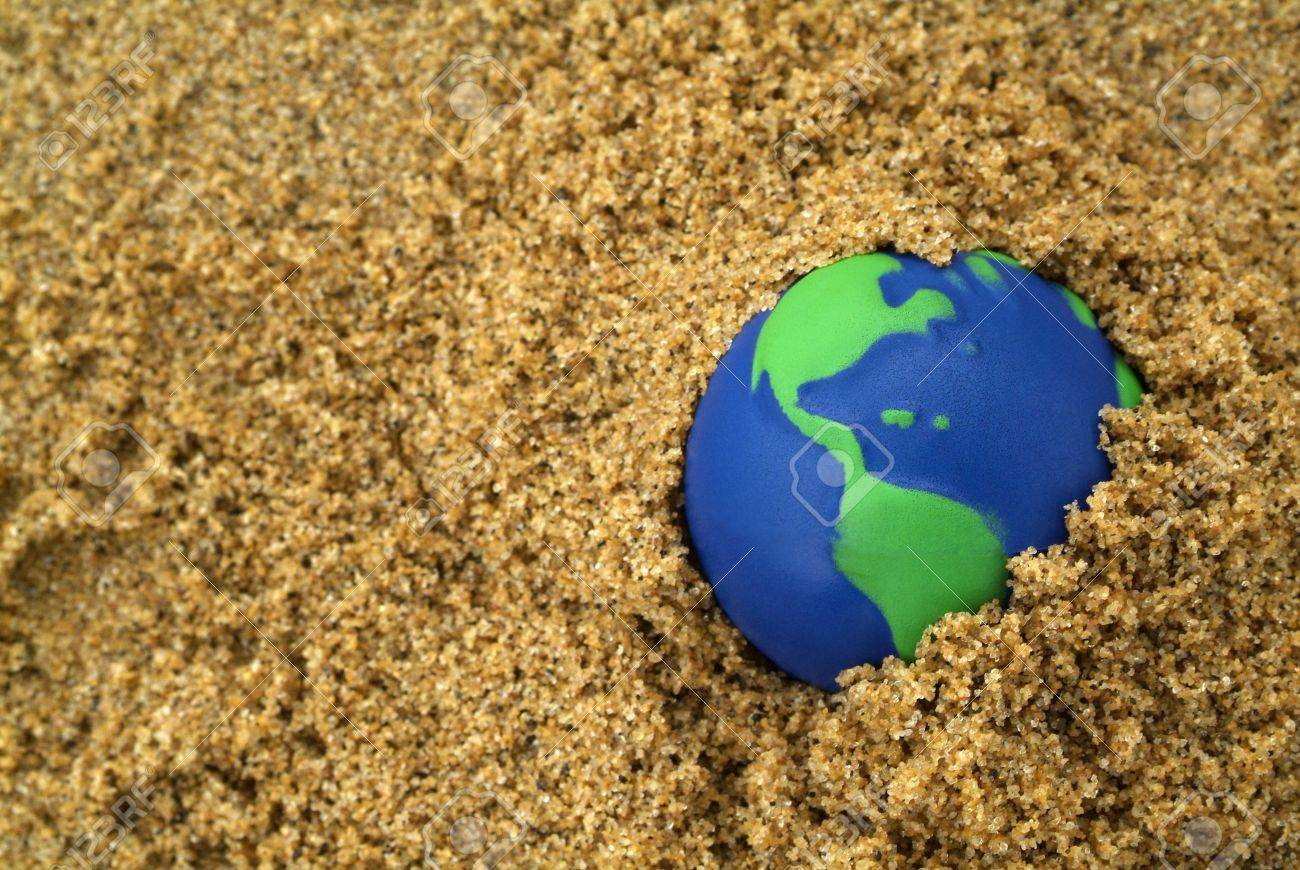 blue and green globe buried in sand Stock Photo - 2856710