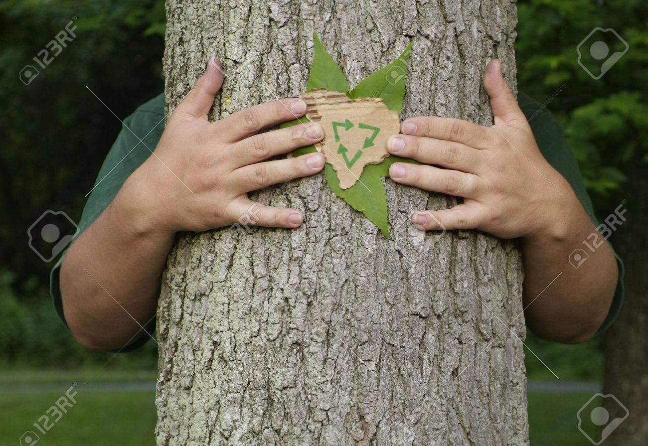 Person wrapping their arms around a tree holding a leaf and a recycling symbol on recycled cardboard Stock Photo - 5091482