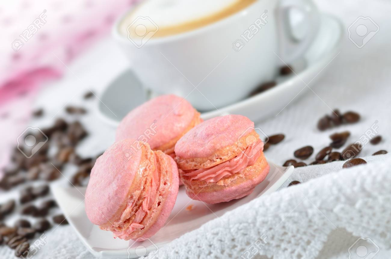 Fine pink macaroons with a cup of cappuccino Stock Photo - 17696322