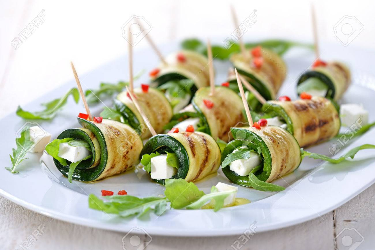 Delicious rolls of fried zucchini slices and feta cheese with arugula, served with olive oil and pieces of bell peppers Banque d'images - 44161216