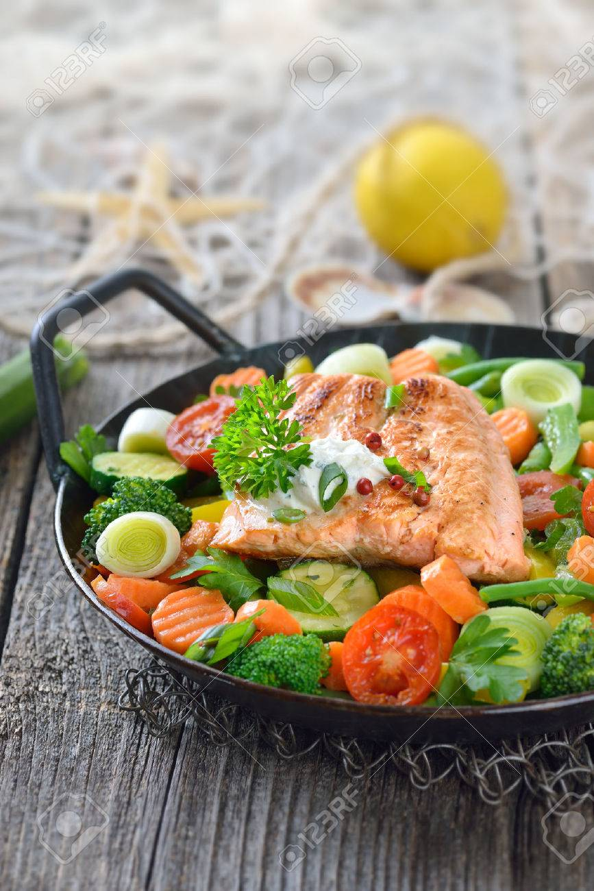 Tasty fried and grilled salmon fillet on mixed vegetables served in a colorful frying pan, lemons and a fishing net in the background Banque d'images - 47223871