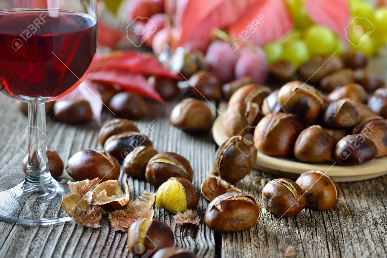 Châtaignes grillées avec du Tyrol du Sud vin rouge sur une vieille table en bois Banque d'images - 47223950