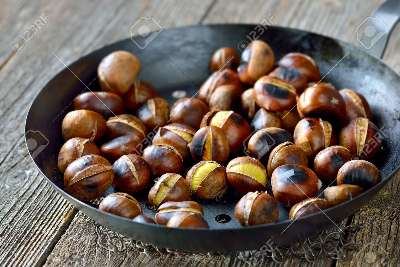 Roasted chestnuts served in a special perforated chestnut pan on an old wooden table Banque d'images - 47742876