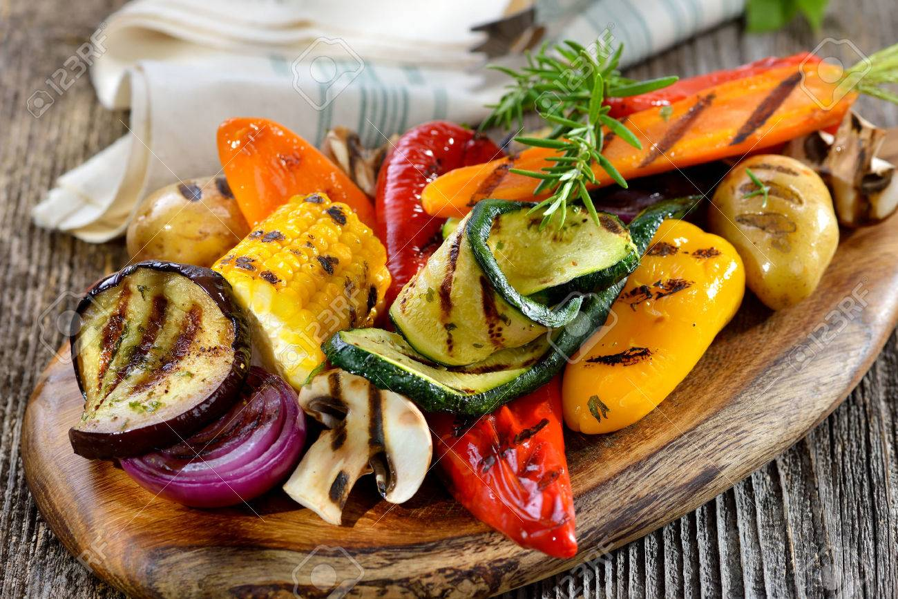 Vegan cuisine: Grilled mixed vegetables on a wooden cutting board Banque d'images - 62812594