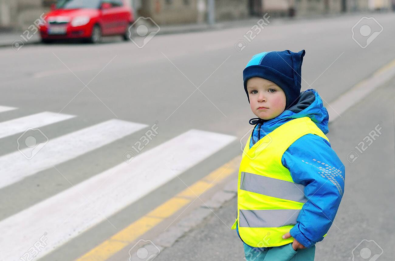 Child in front of pedestrian crossing. A little boy finds out if he can cross the crossswalk. He wears reflective vest because of safety. Car in the background. Child concept. Traffic concept. - 133443644